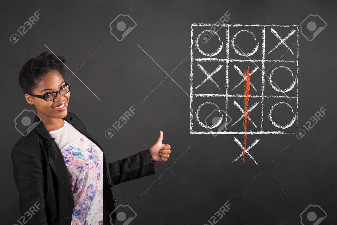 South African or African American black woman teacher or student with a thumbs up hand signal with tic tac toe standing against a chalk blackboard background inside - 45231853