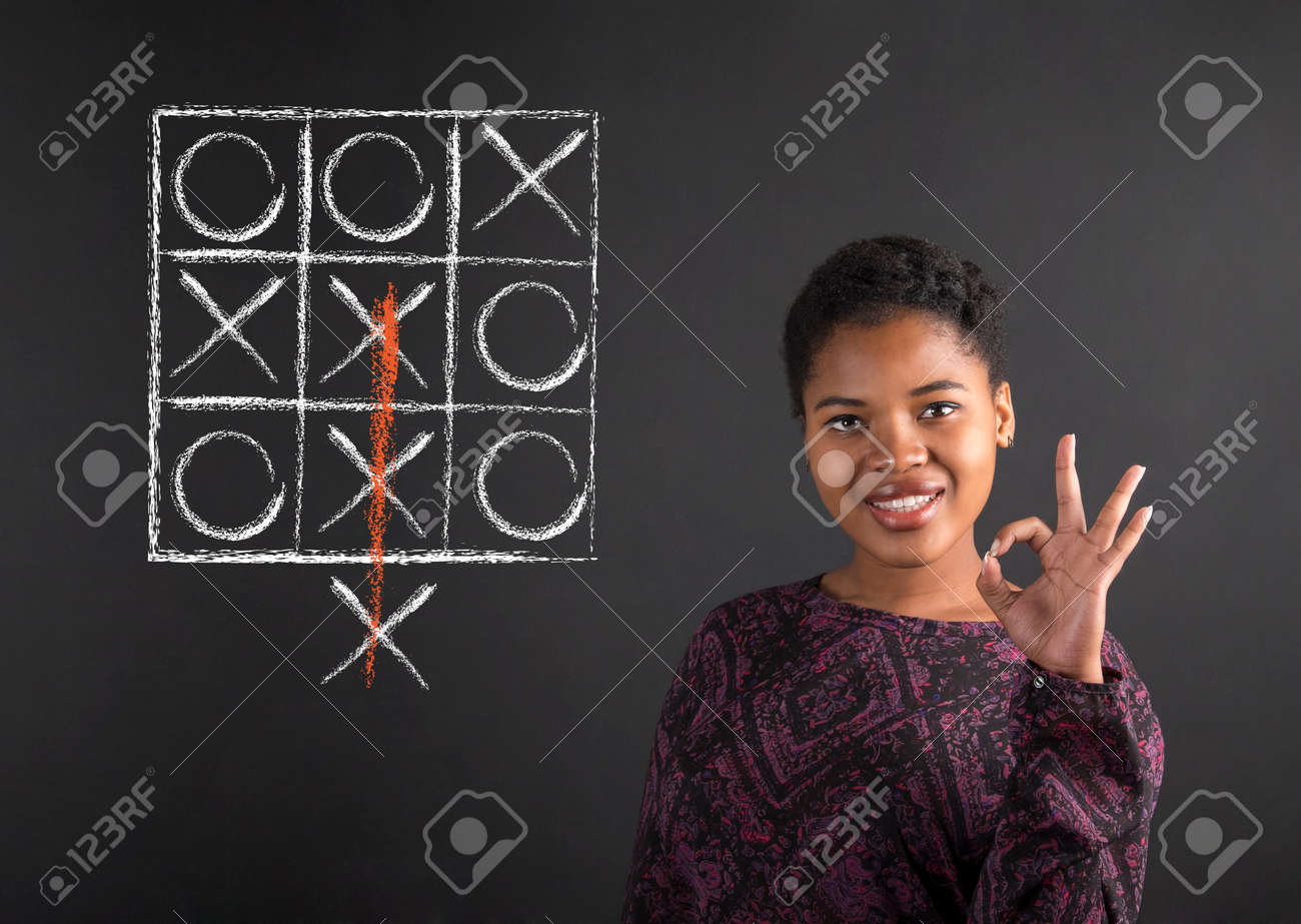 South African or African American black woman teacher or student holding up a perfect hand signal with a tic tac toe diagram on a chalk blackboard background inside - 45232067