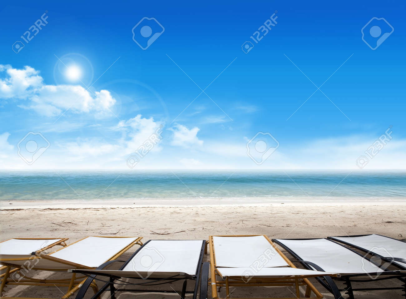 Tropical beach with deck chairs on the ocean and blue sky with clouds in the background Stock Photo - 13965081