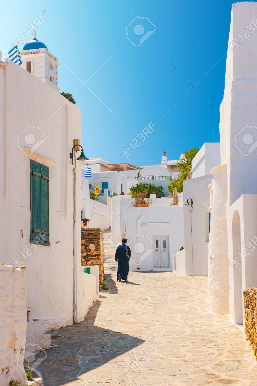 Greek Orthodox priest walking in an alleyway on the island of Sifnos Stock Photo - 15124798