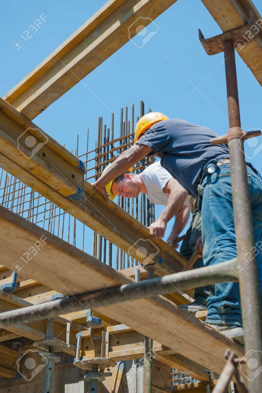 Authentic construction workers placing slab formwork beams in construction site Stock Photo - 15693315