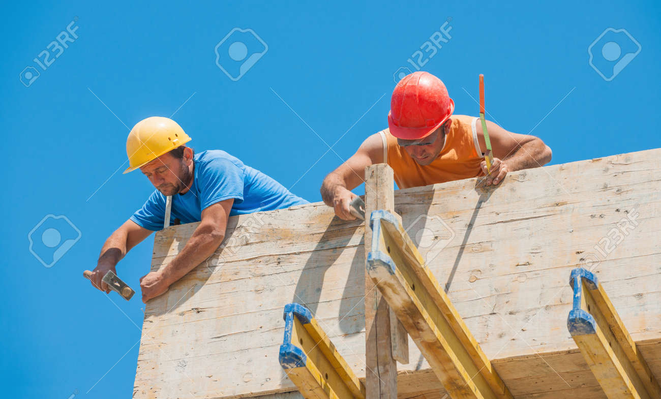 Authentic construction builders working together for nailing wooden cement formwork in place Stock Photo - 15730548