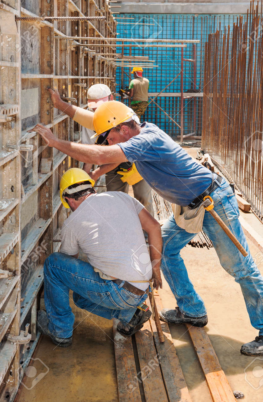 Authentic construction builders working together for positioning concrete formwork frames in place Stock Photo - 15812268