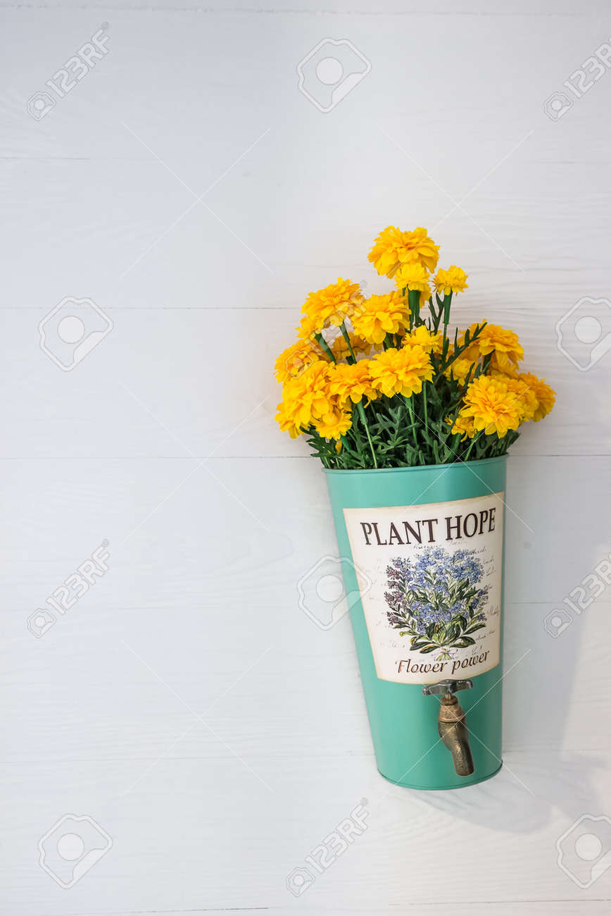 Flower Pot With Yellow Flowers Hanging On A House Wall Stock Photo