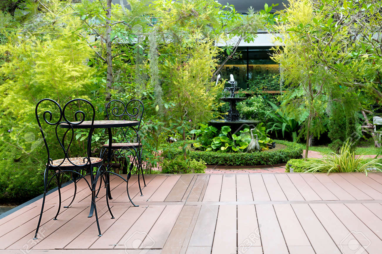 Black chair in wood patio at green garden with fountain in house. Outdoor garden. - 66005682