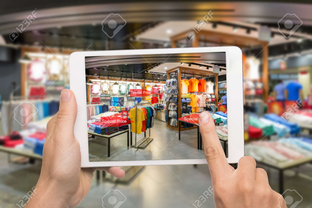 Augmented reality marketing concept. Hand holding digital tablet smart phone use AR application to check special sale price in retail fashion shop mall - 66458465
