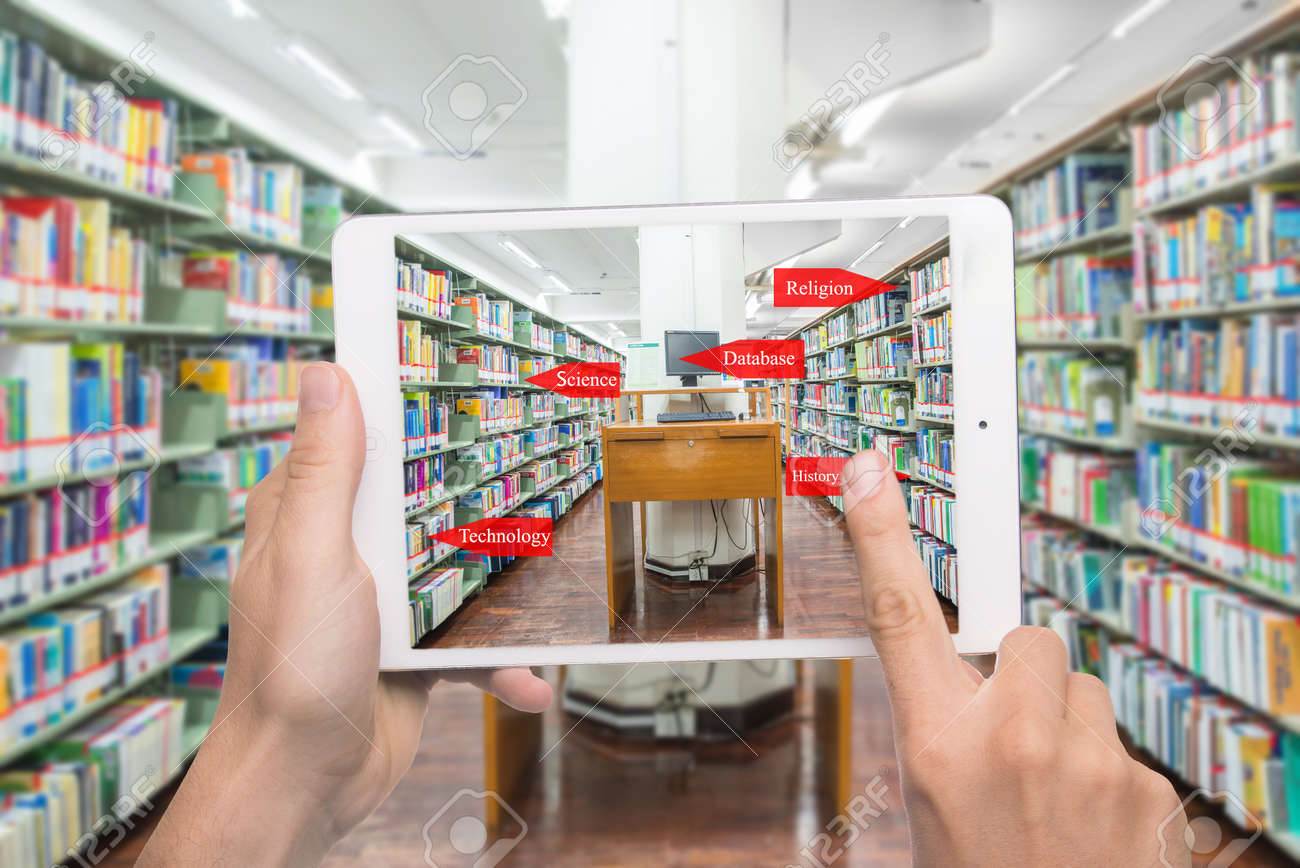 Augmented reality education concept. Hand holding digital tablet smart phone use AR application to check library category in bookshelf at university library. - 74276748