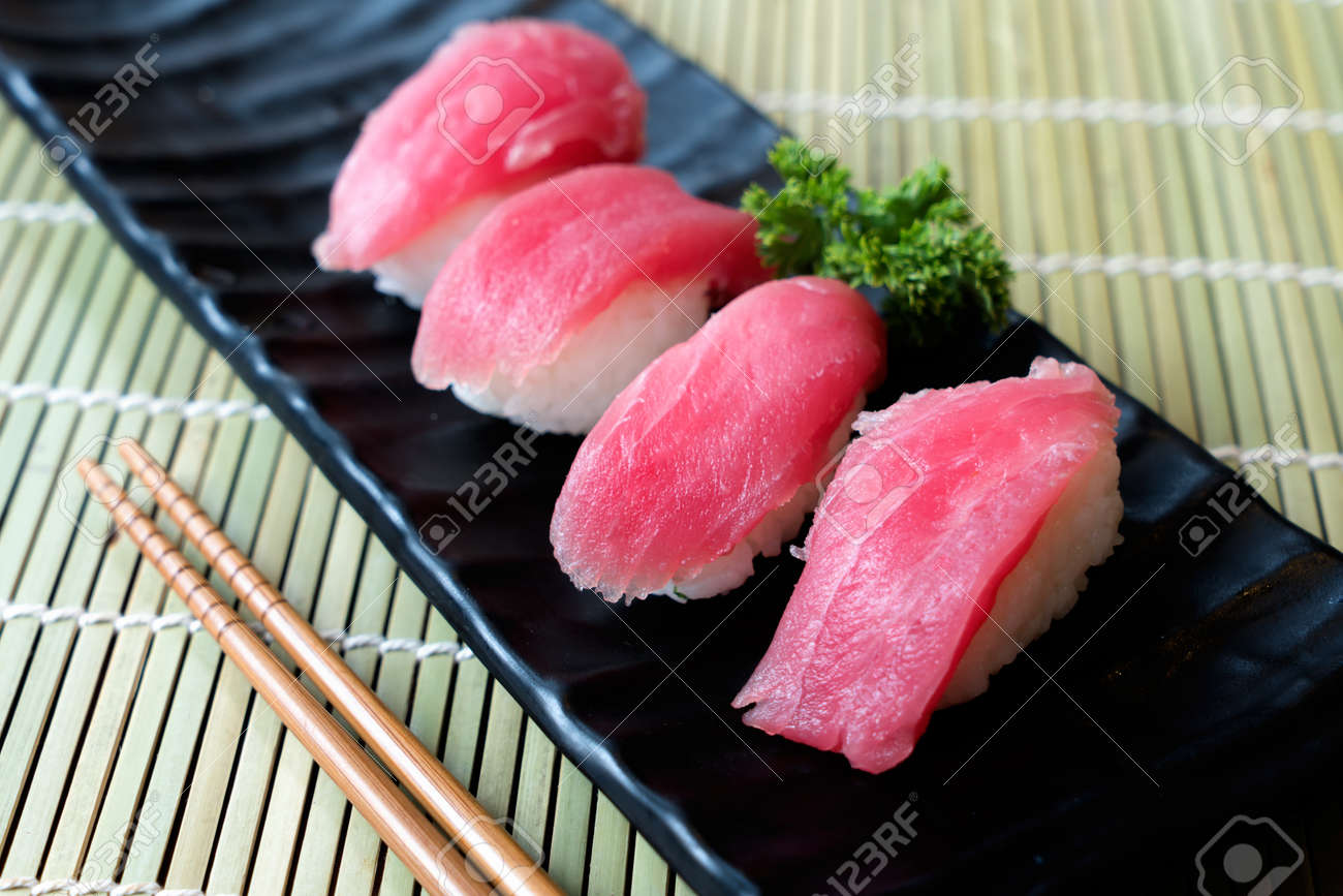 Tuna Sushi On Black Plate Along With Japanese Sauce And Green Leaf