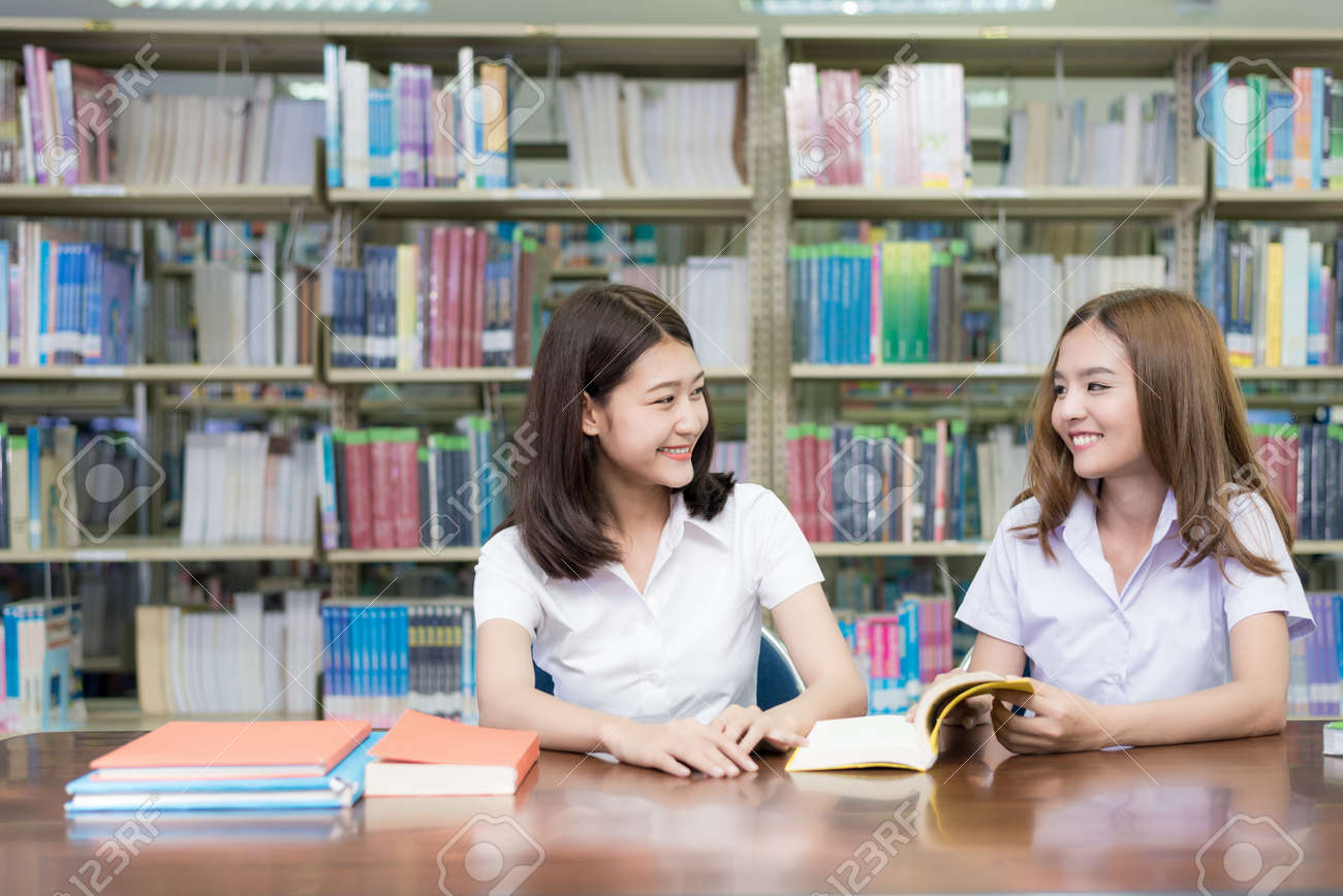 Two Asian students studying together in library at university. University student. - 126107529