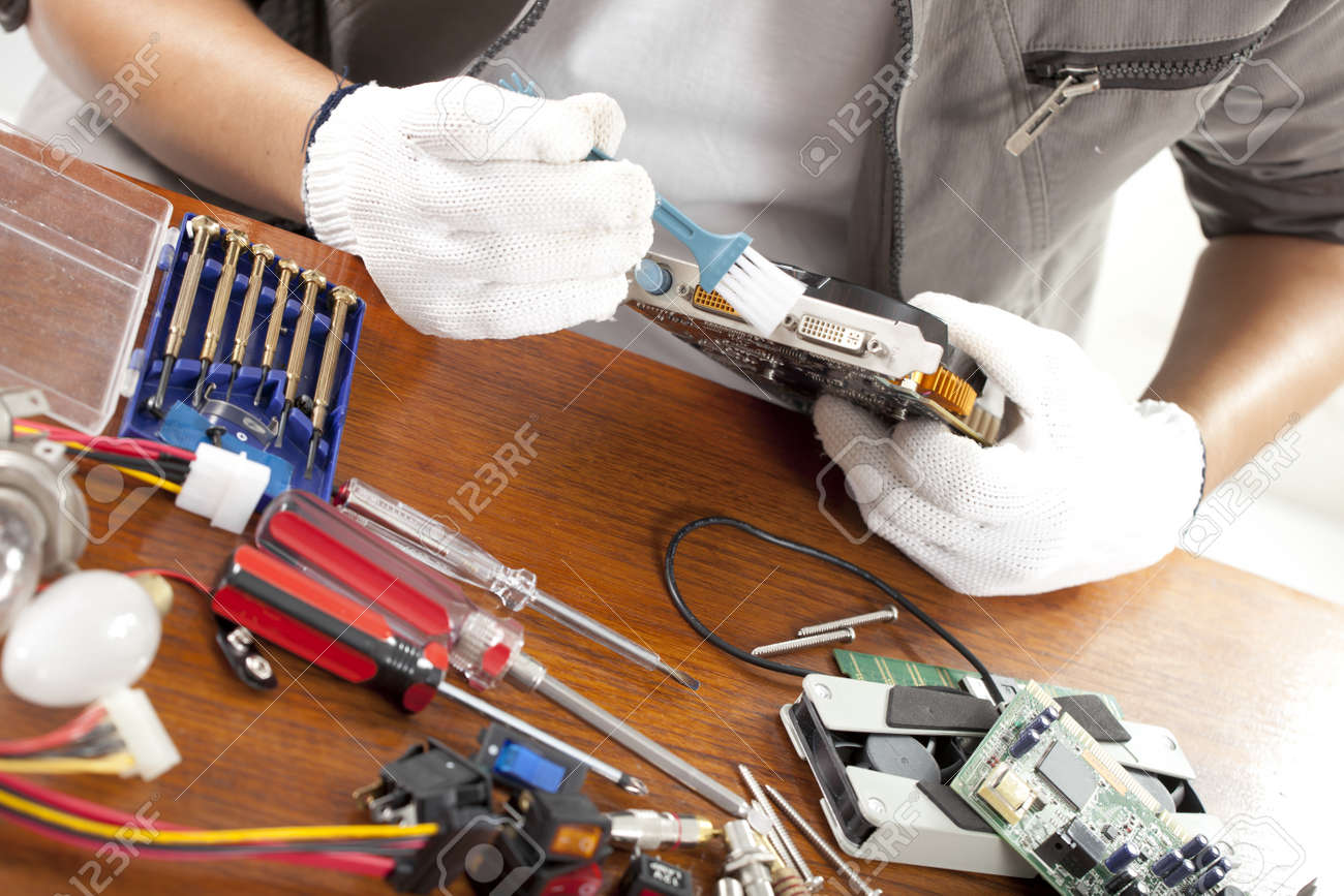 Repair man engineer fixing computer part on work table stock photo repair man engineer fixing computer part on work table stock photo 21585788 greentooth Image collections