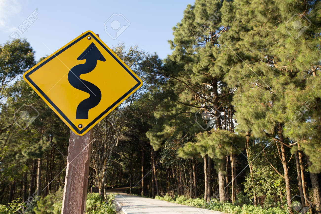 Winding road signyellow winding road ahead sign in pine wood winding road signyellow winding road ahead sign in pine wood mountain street stock photo publicscrutiny Images