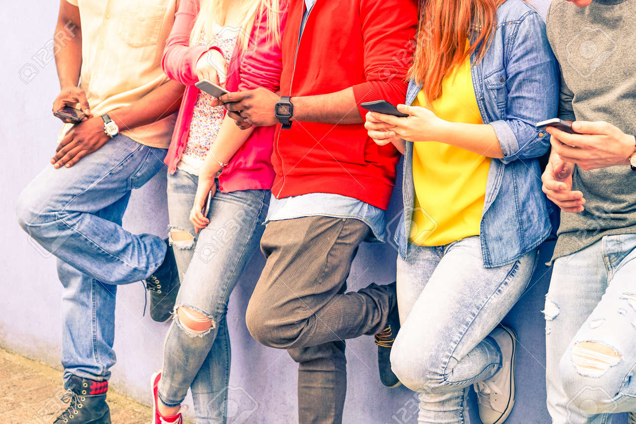Multiracial group of friends texting sms and looking down to cell phone - Interracial students hands using mobile - Concept of young people addiction to web technology - Focus on hand of red hair girl - 55465884