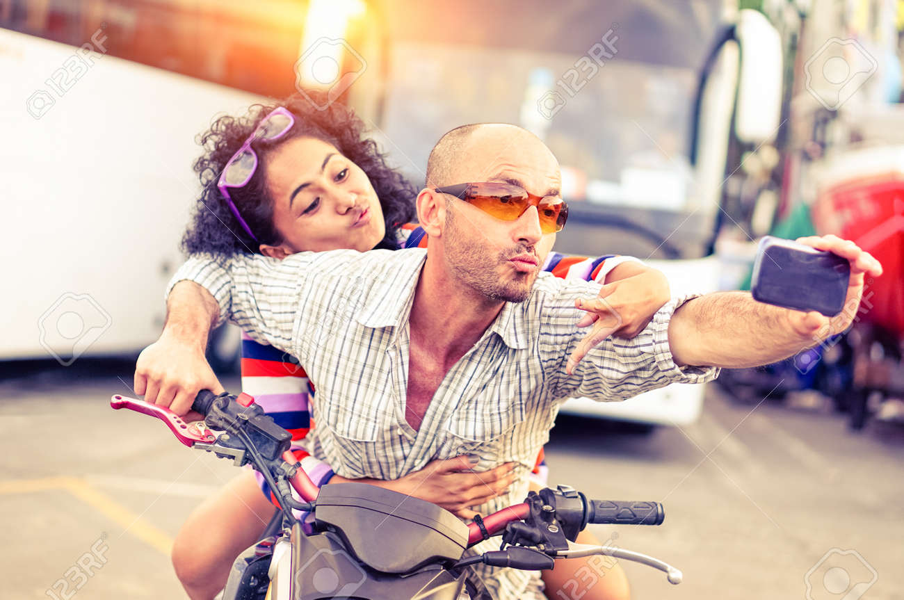 Couple of bikers taking selfie riding motorbike on urban road at sunset - Cool man and beautiful girl on sport motorcycle with funny facial expression - Concept of dangerous drive - Focus on male - 56299790