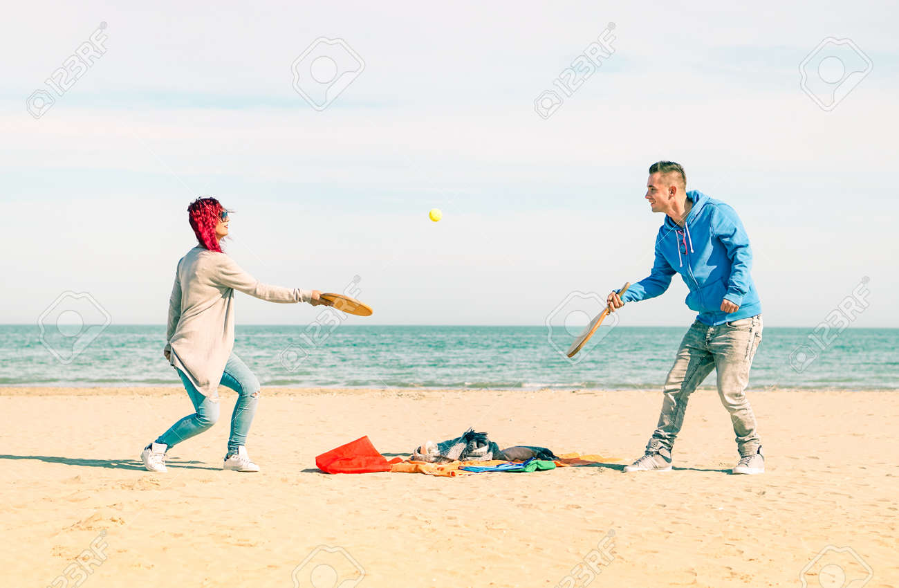 Couple playing beach tennis game on the sand with blue ocean and sky background - Playful young friends having fun with healthy recreation on summer holiday - Concept of  joyful moment and active life Standard-Bild - 56299825