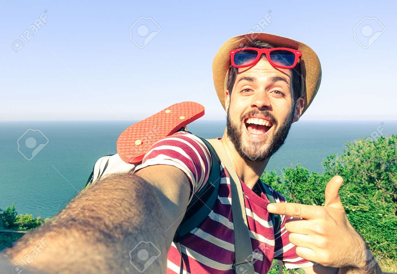 Young man taking travel selfie on trekking excursion day - Hipster guy self photo at view point with blue ocean background - Concept of healthy lifestyle in beauty of nature - Soft vintage filter look - 58920904