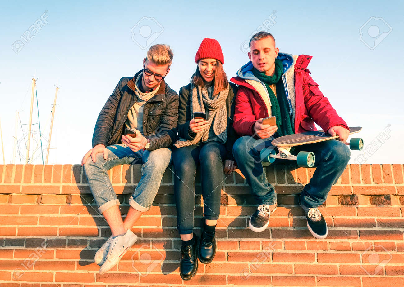 Group of friends using smartphone sitting on low briks wall - Young people addicted to mobile technology with disinterest talking each other - Teenagers holding telephone outdoor - Concept of leisure - 66154355