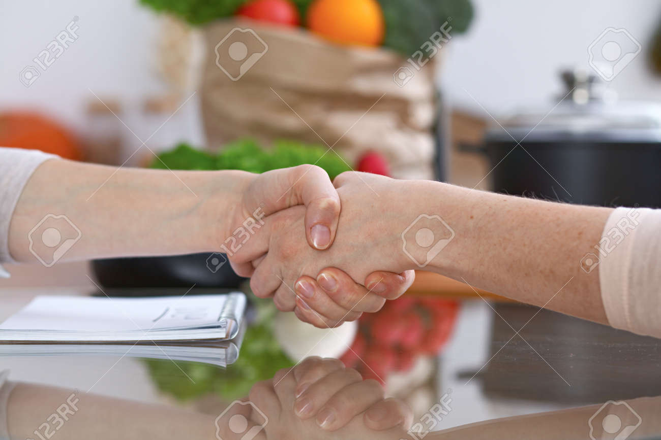 Close-up Of Shaking Hands Over A Table In The Kitchen. Friends ... on kitchen backsplash, kitchen bathroom, kitchen family, kitchen vintage, kitchen classroom, kitchen farm, kitchen tile,
