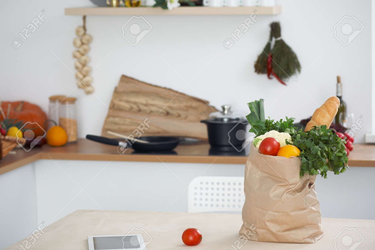 paper bag full of vegetables on the table in kitchen interiors
