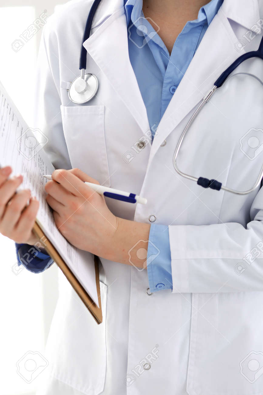 Female doctor using medical form on clipboard closeup. Physicianat work in hospital or clinic. Healthcare, insurance and medicine concept - 121621211