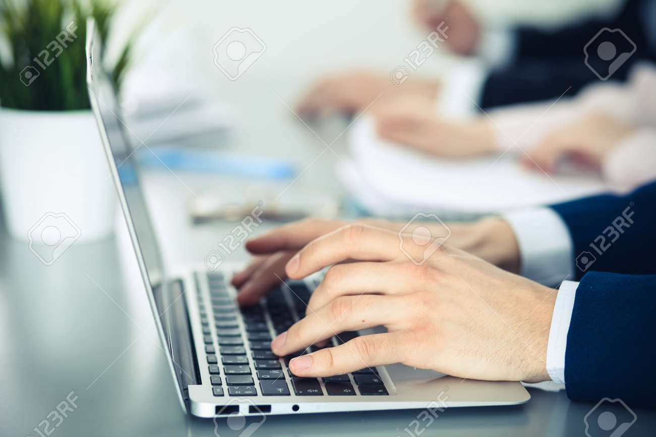 Group of business people working together in office. Man hands typing on laptop computer - 121349539
