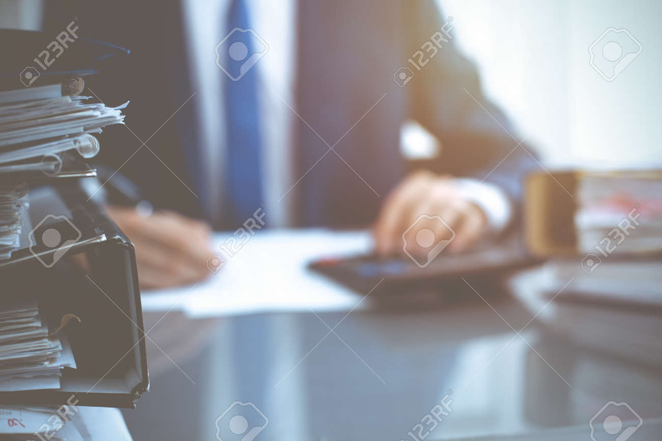 Binders with papers waiting to be processed with businessman or bookkeeper back in blur. Accounting planning budget. Audit, insurance and business concept - 121934718