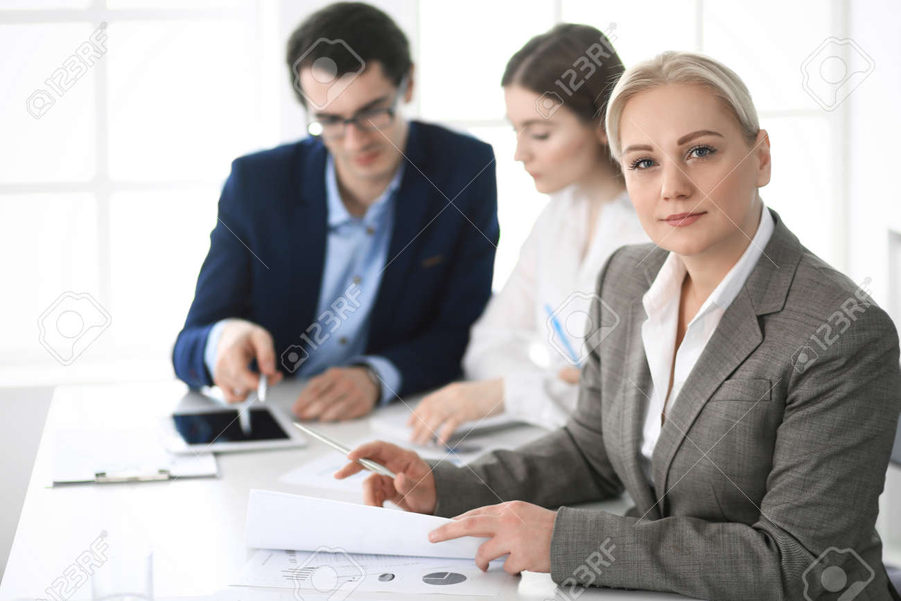 Headshot of business woman at negotiation. Group of business people discussing questions at meeting in modern office. Teamwork, partnership and business concept - 123037972