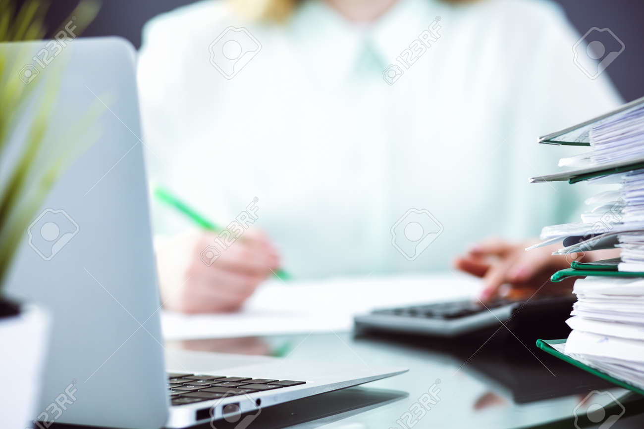 Bookkeeper or financial inspector making report, calculating or checking balance. Audit and tax service concept. Green colored image background. - 129470345