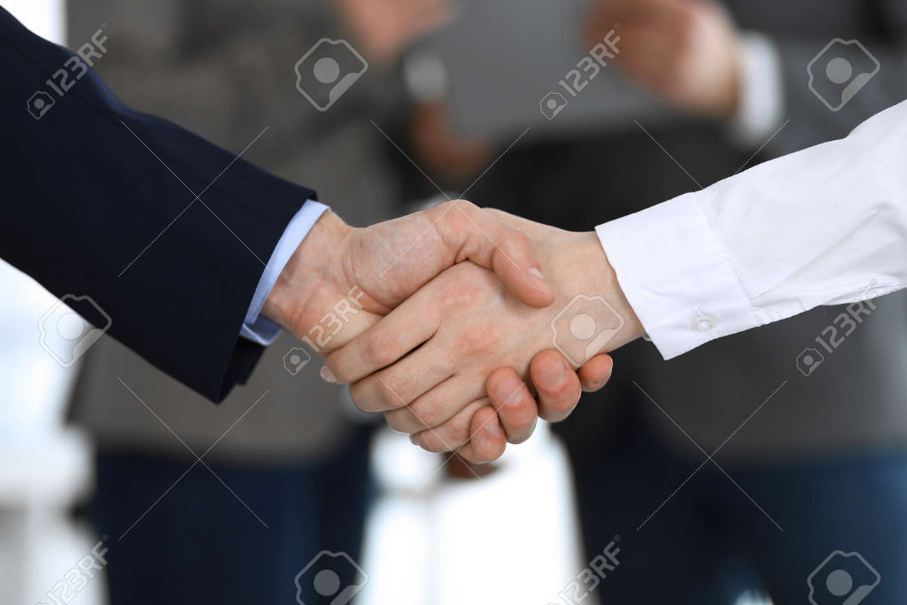 Business people shaking hands while standing with colleagues after meeting or negotiation, close-up. Group of unknown businessmen and women in modern office. Teamwork, partnership and handshake concept, toned picture - 134025989