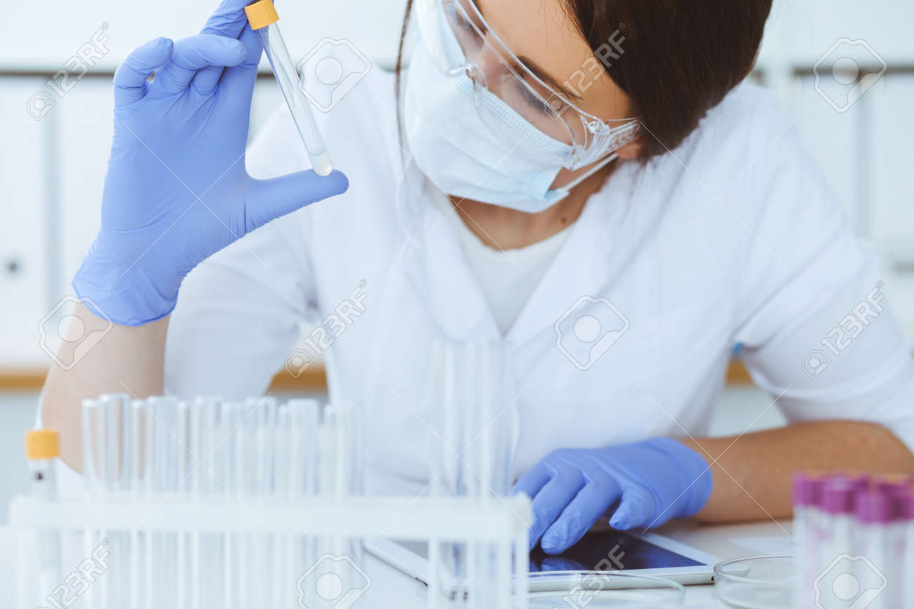 Close-up of professional female scientist in protective eyeglasses making experiment with reagents or blood test in laboratory. Medicine, biotechnology and research concept. - 138528428