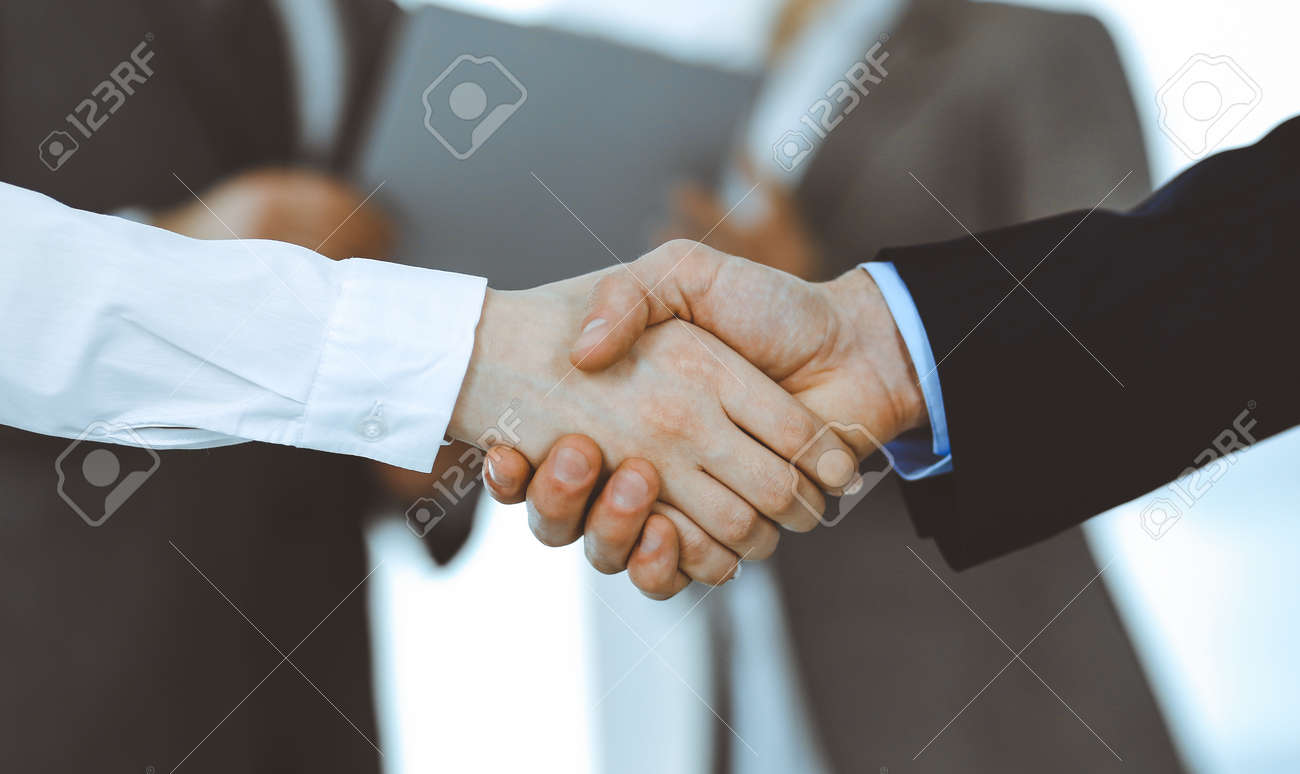 Business people shaking hands while standing with colleagues after meeting or negotiation, close-up. Group of unknown businessmen and women in modern office. Teamwork, partnership and handshake concept, toned picture. - 139656025