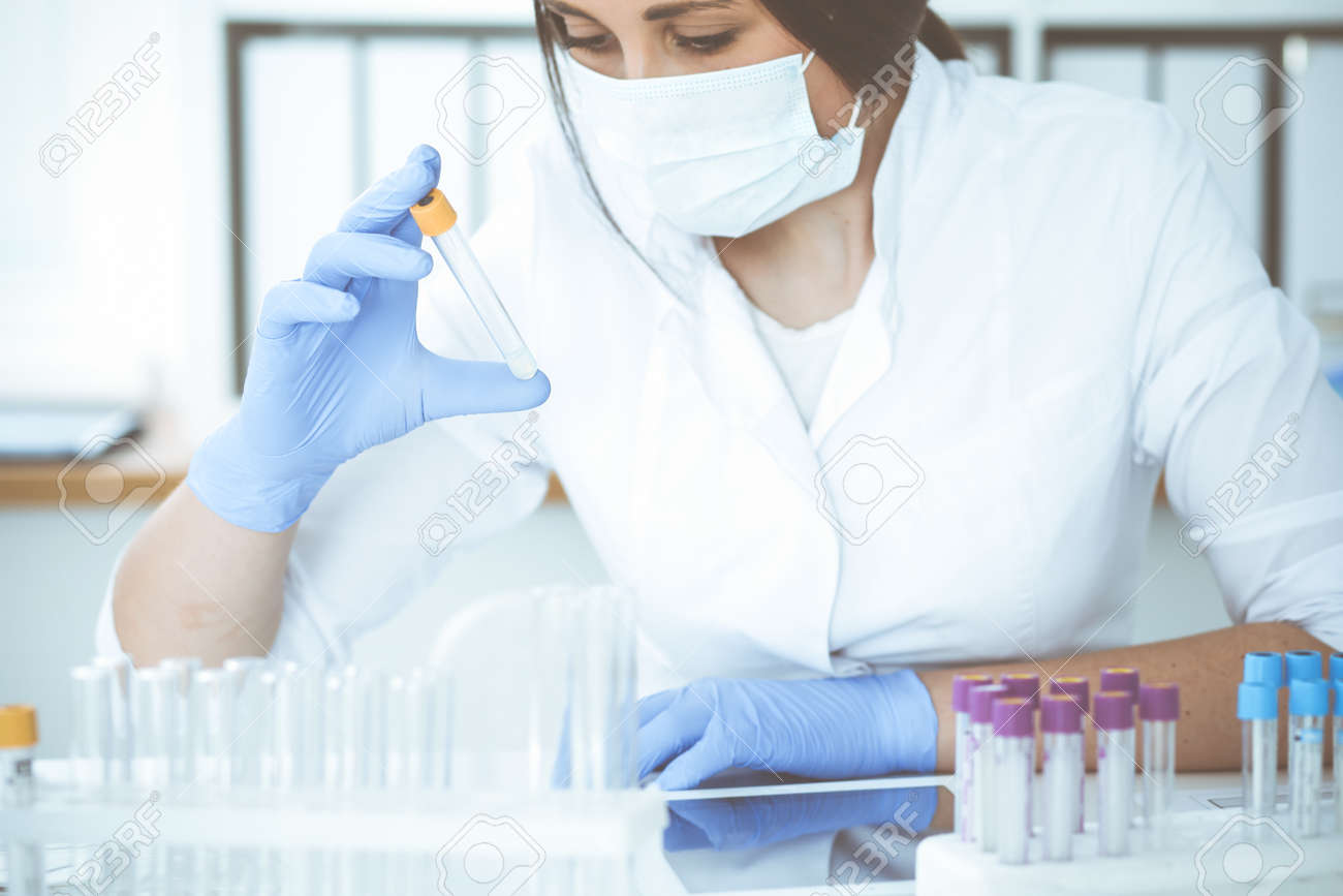 Close-up of professional female scientist in protective eyeglasses making experiment with reagents or blood test in laboratory. Medicine, biotechnology and research concept. - 140707771