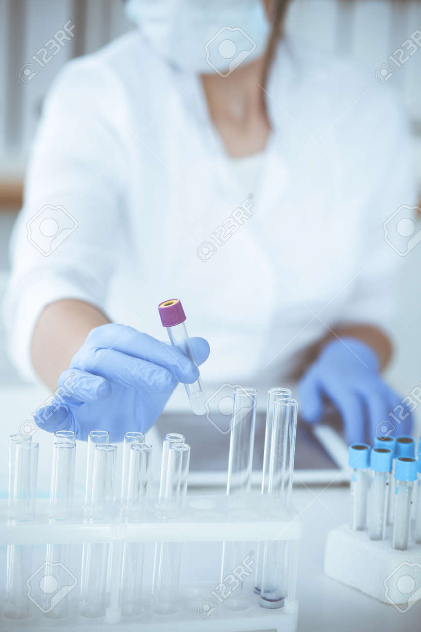 Close-up of professional female scientist in protective eyeglasses making experiment with reagents or blood test in laboratory. Medicine, biotechnology and research concept. - 140707828