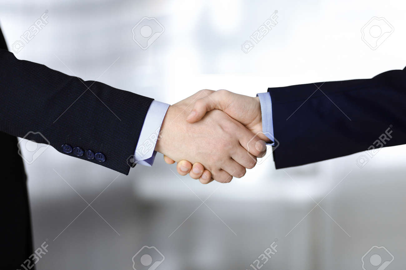 Business people shaking hands, close-up. Group of unknown businessmen standing in a modern office. Teamwork, partnership and handshake concept - 150779411