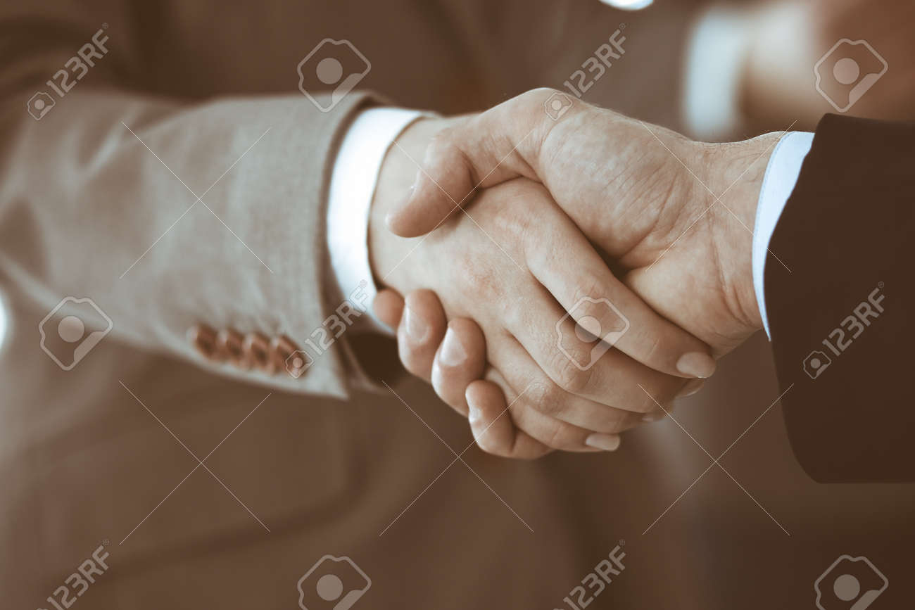 Business people shaking hands while standing with colleagues after meeting or negotiation, close-up. Group of unknown businessmen and women in modern office. Teamwork, partnership and handshake concept, toned picture. - 157763826