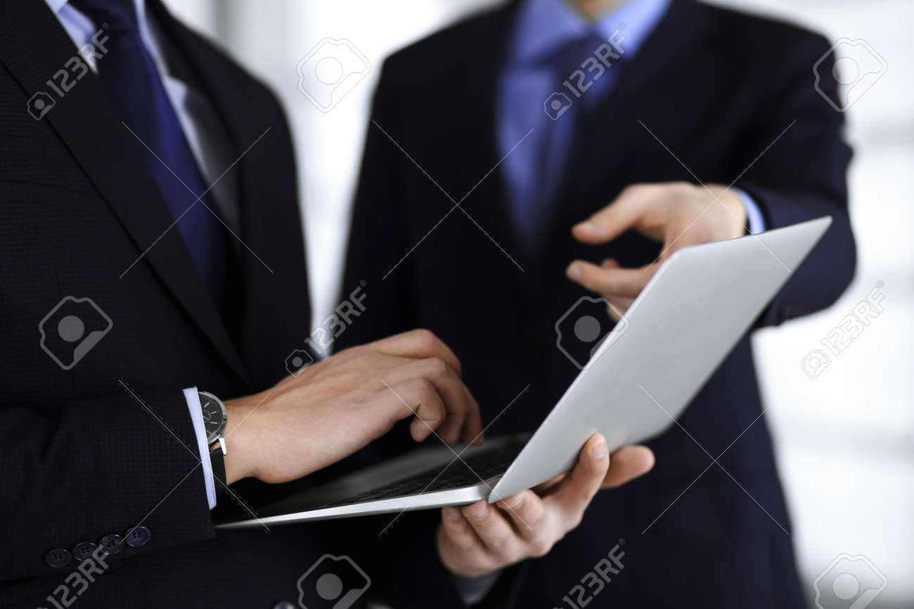 Business people use a tablet computer for discussion of their new project, standing in a modern office. Unknown businessman or male entrepreneur with a colleague at workplace. Teamwork and partnership concept. - 165229328