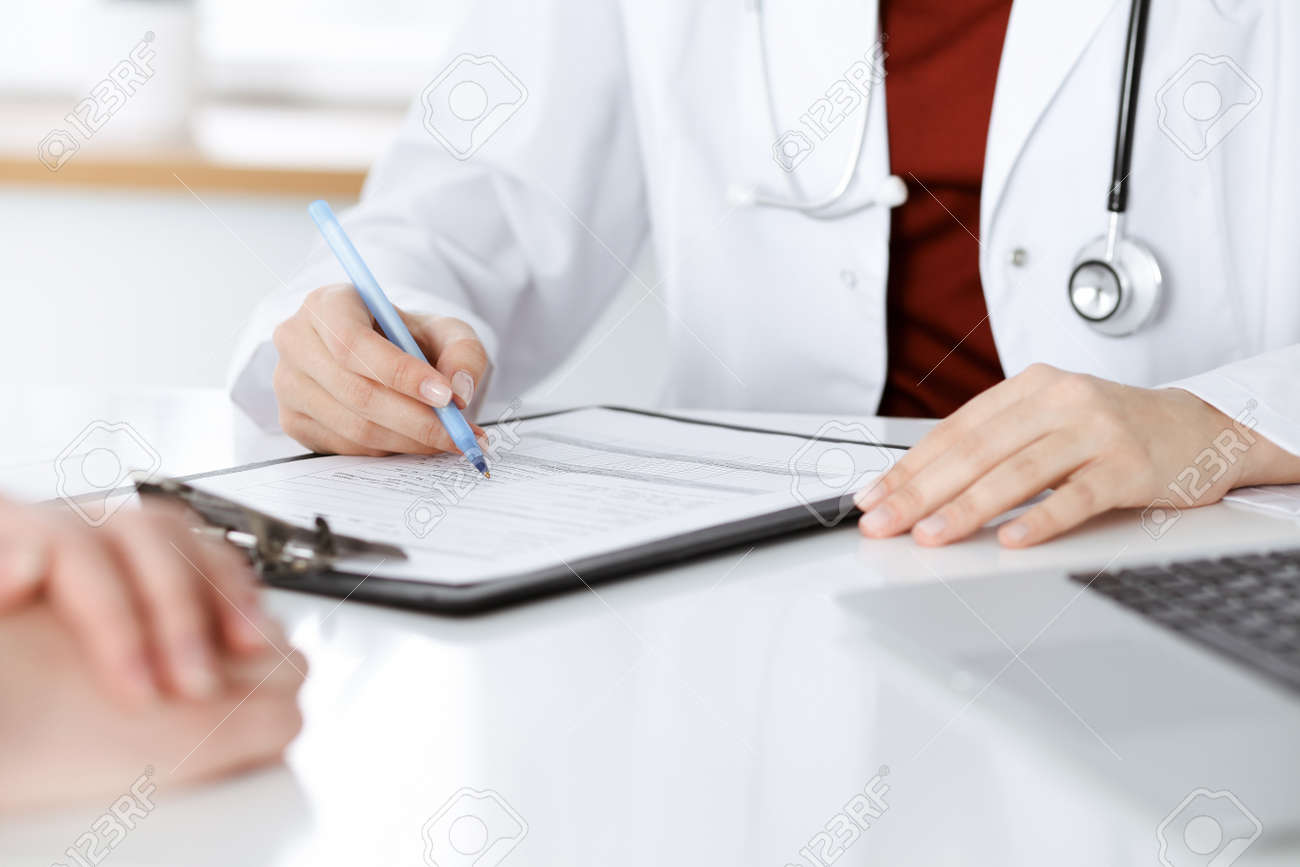 Unknown woman-doctor consulting patient and using clipboard with a medication history record. Medicine concept - 166188905