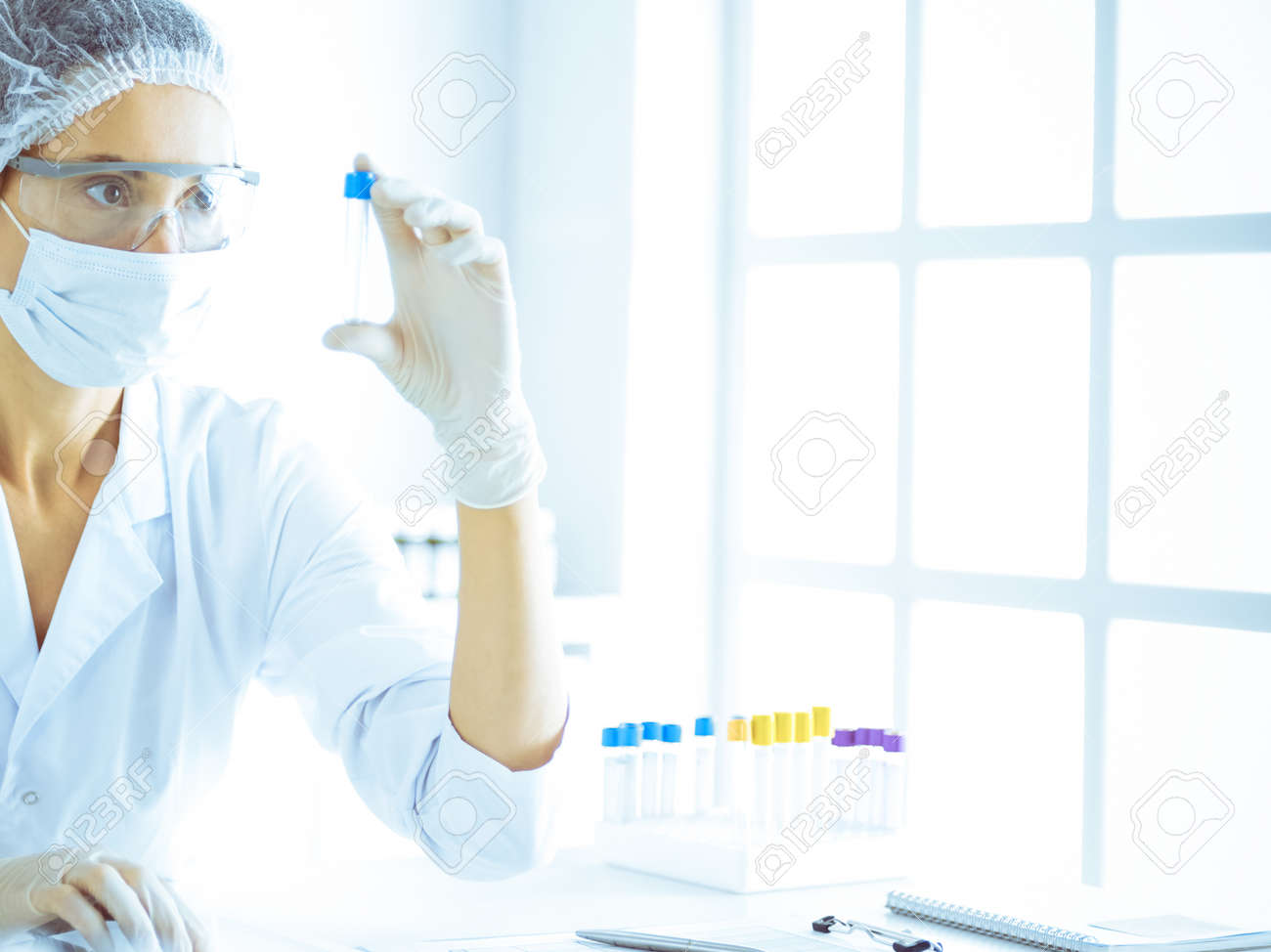 Professional female scientist in protective eyeglasses researching tube with reagents in laboratory toned in blue. Concepts of medicine and science researching - 166676079