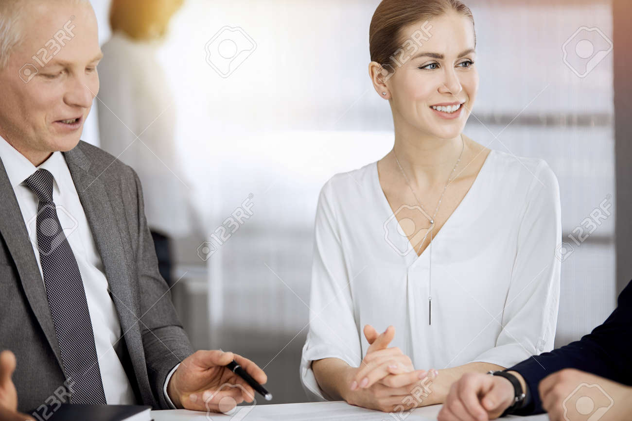 Elderly businessman and group of business people discussing contract in sunny office. Teamwork and cooperation - 167021820