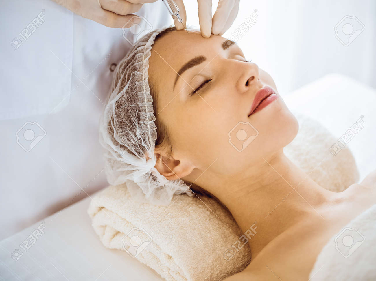 Beautiful woman receiving beauty injections with closed eyes in medical center. Beautician doctor hands doing beauty procedure to female face with syringe. Cosmetic medicine and surgery concept - 167677639