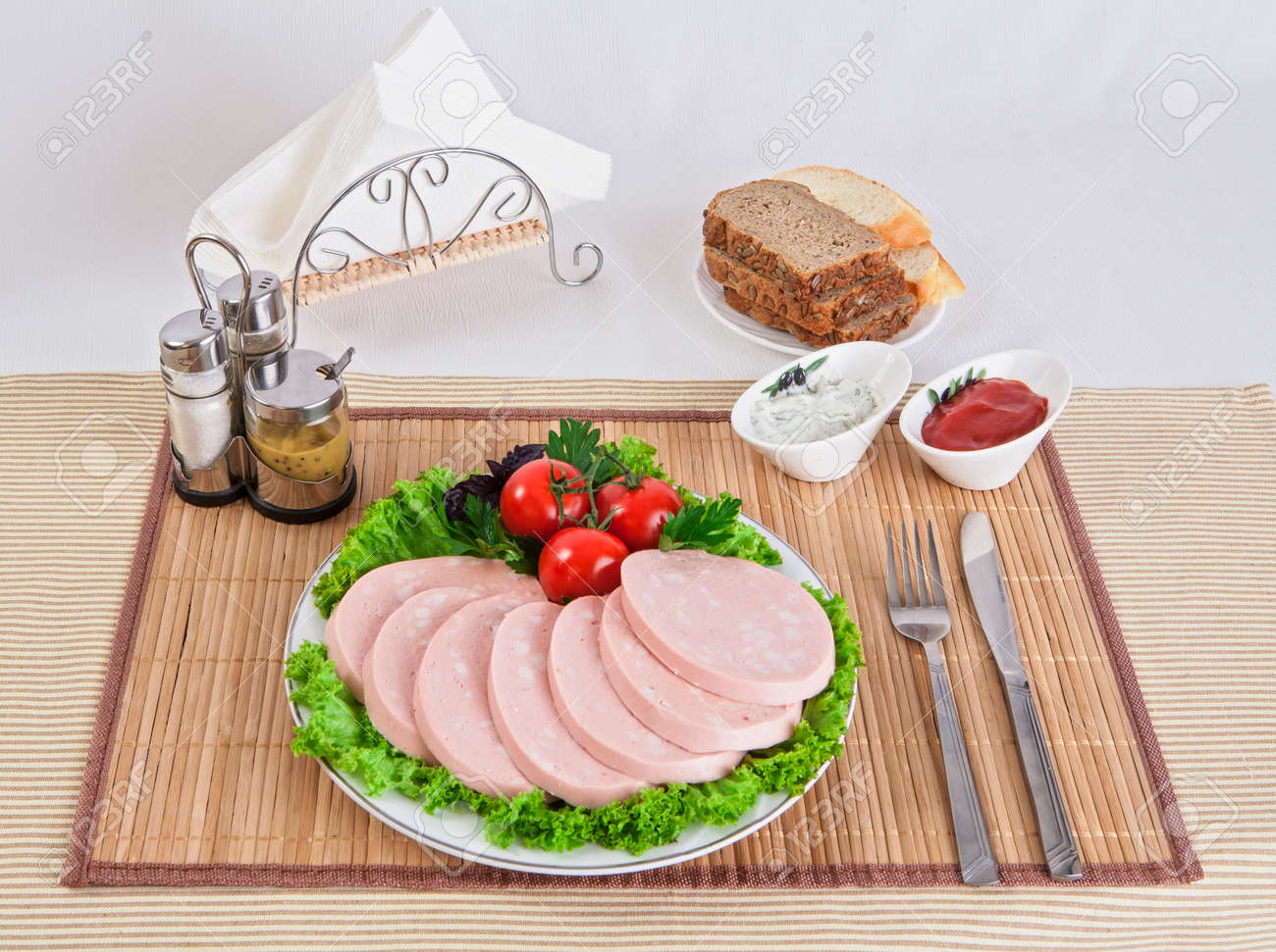 Sliced boiled sausages with tomatoes on lettuce leaves are laid