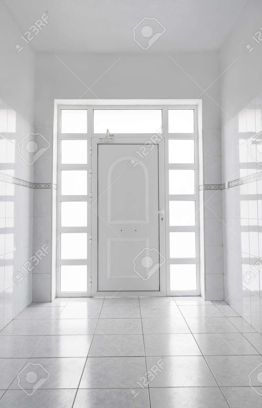 Espace Entre Porte Et Carrelage hall d'entrée avec murs blancs et carrelage en marbre blanc. la porte  blanche a un cadre en verre qui laisse entrer la lumière du jour dans le  hall.