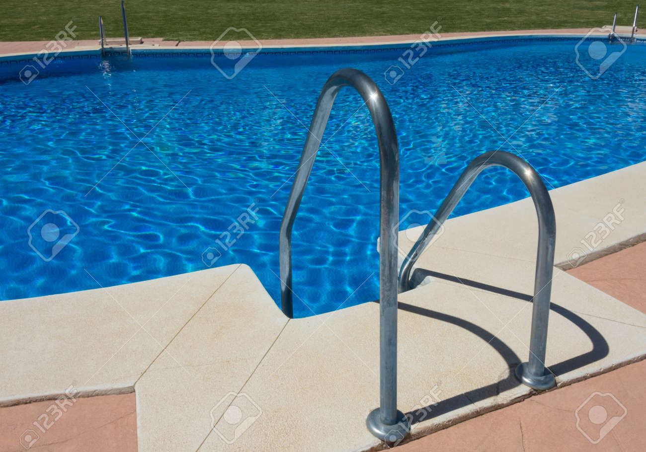 Clean swimming pool without people, with steel staircase and..