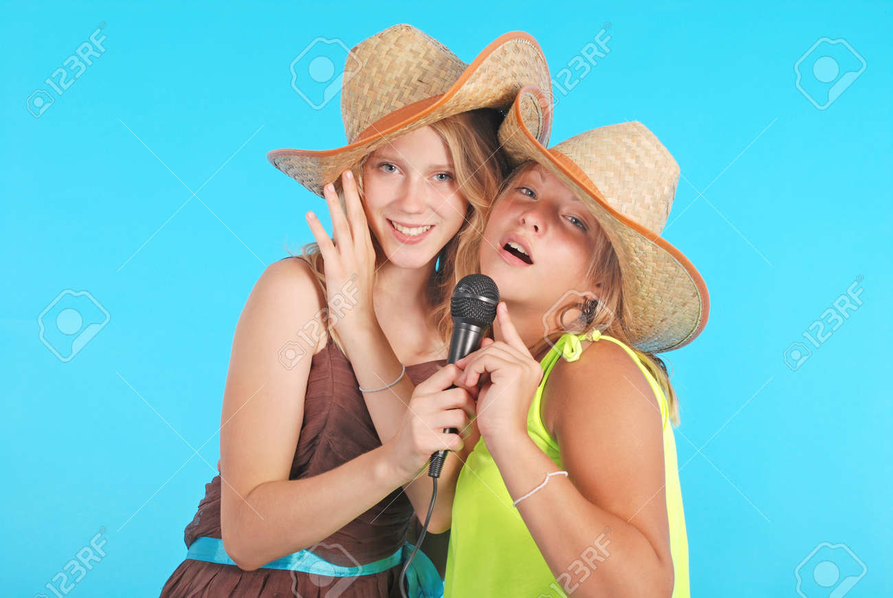 1b157b39e87 Stock Photo - Two pretty thirteen year old girls wearing a big floppy straw  sun hat isolated on blue