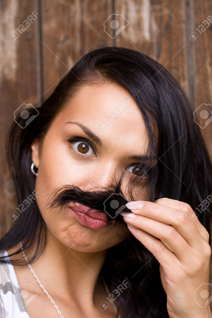 A glamour close-up of a funny young brunette placing her hair under her nose as if mimicking a moustache Stock Photo - 13997702