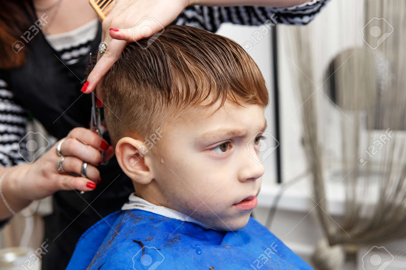 Little Boy Getting Haircut By Barber At Barbershop Stock Photo