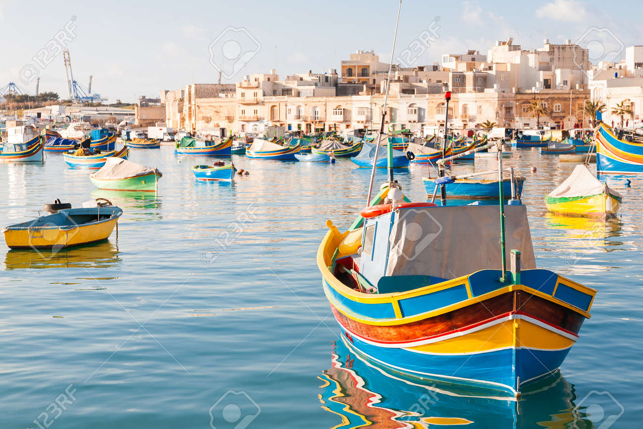 Colorful typical boats - Mediterranean traditional fisherman village in the south east of Malta. Early winter morning in Marsaxlokk, Malta. - 51867246