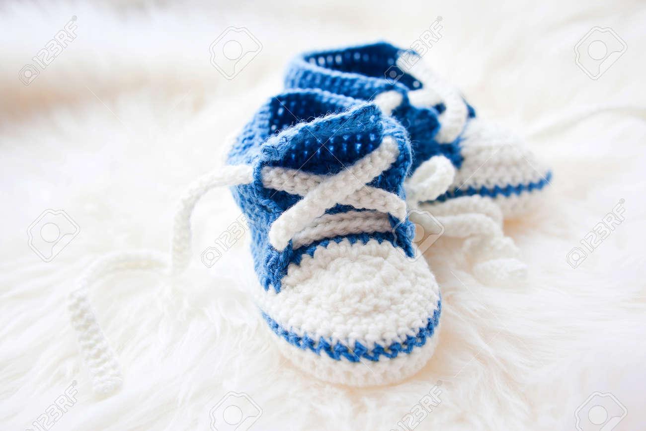 2971b6319bbbe Les petites chaussures de bébé. Tricoté premières chaussures de sport pour  garçon nouveau-né