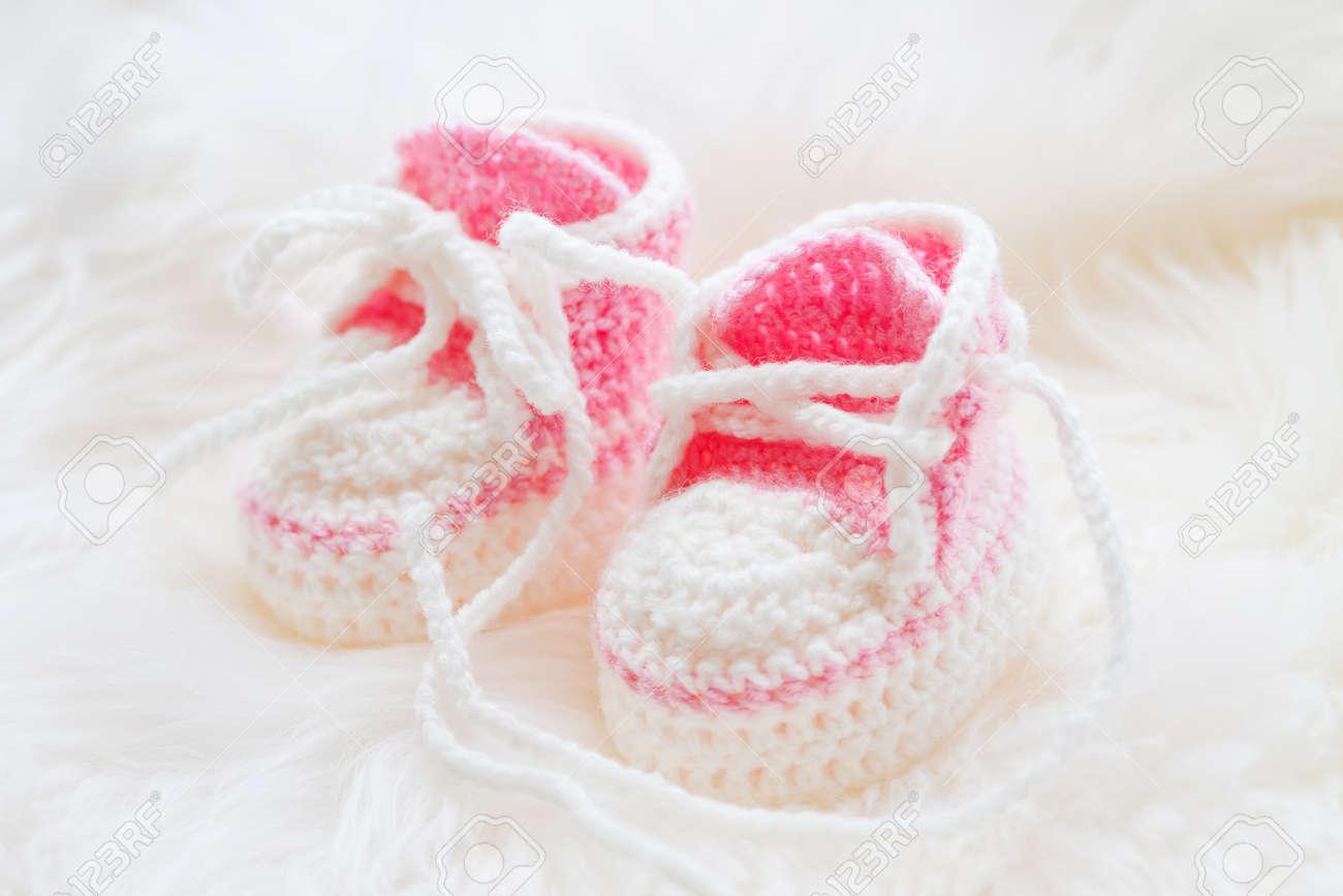 c6da669273403 Banque d images - Les petites chaussures de bébé. Tricotés à la main  premières baskets pour fille nouveau-né. Crochet Chaussons main rose sur fond  blanc ...