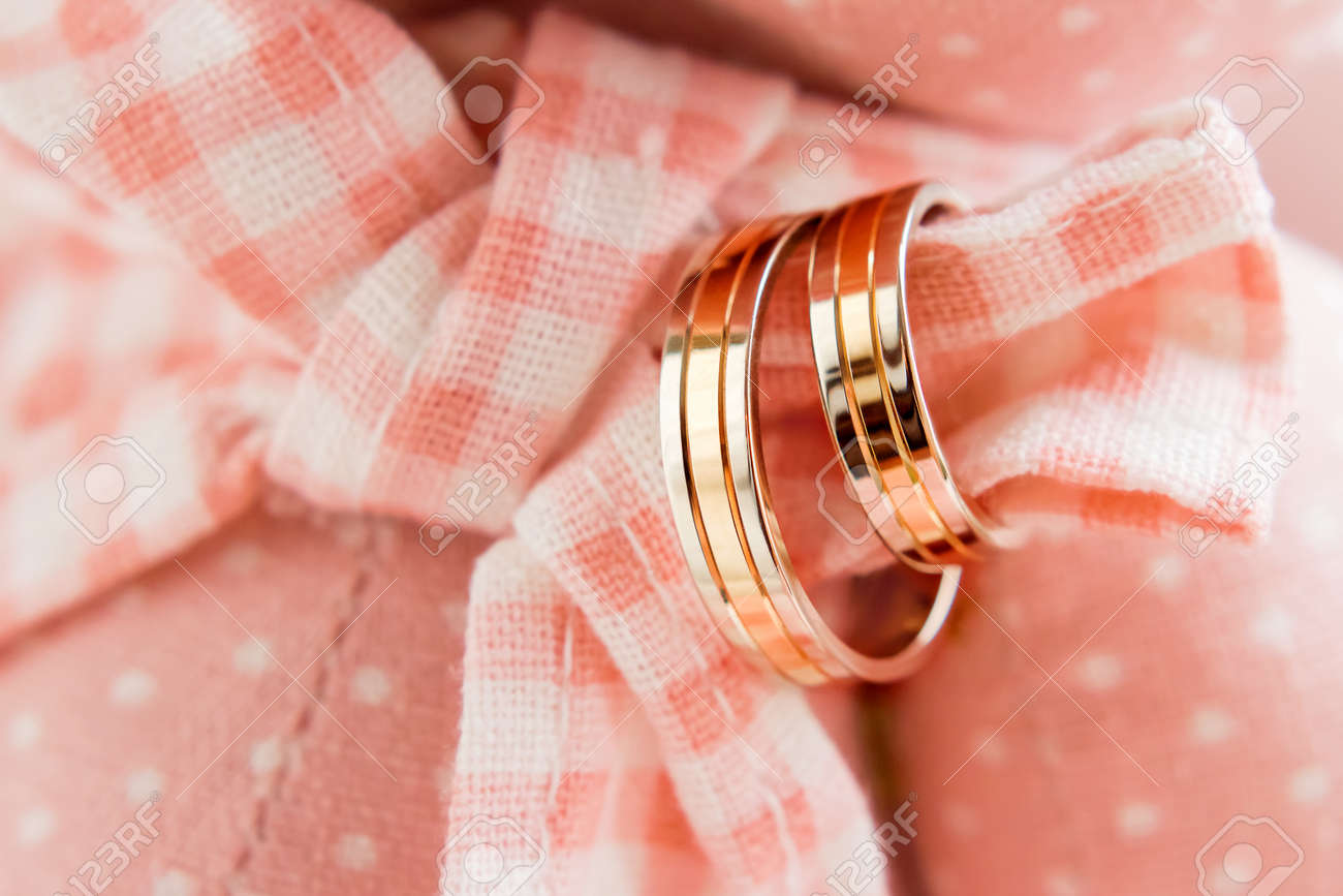 Golden Wedding Rings On Pink Plaid Fabric. Wedding Jewelry Details ...