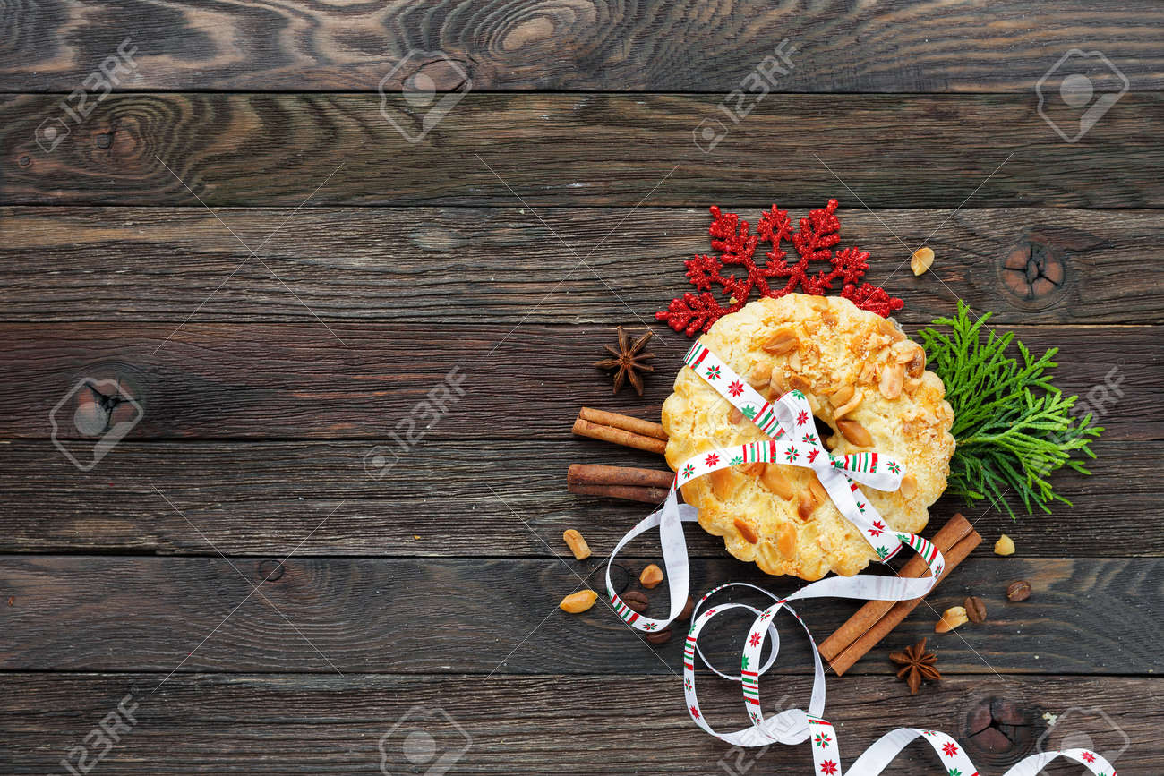 Winter holiday rustic background with peanuts tart and cinnamon. Christmas and New Year decorations - red snowflake, thuja and pine cones. Tasty dessert with colorful ribbon. Top view, flat lay, place for text. - 65061295